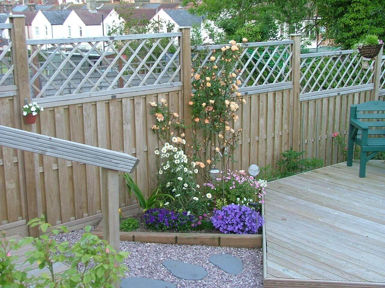 Rose flower bed from landscape timbers and matching fence