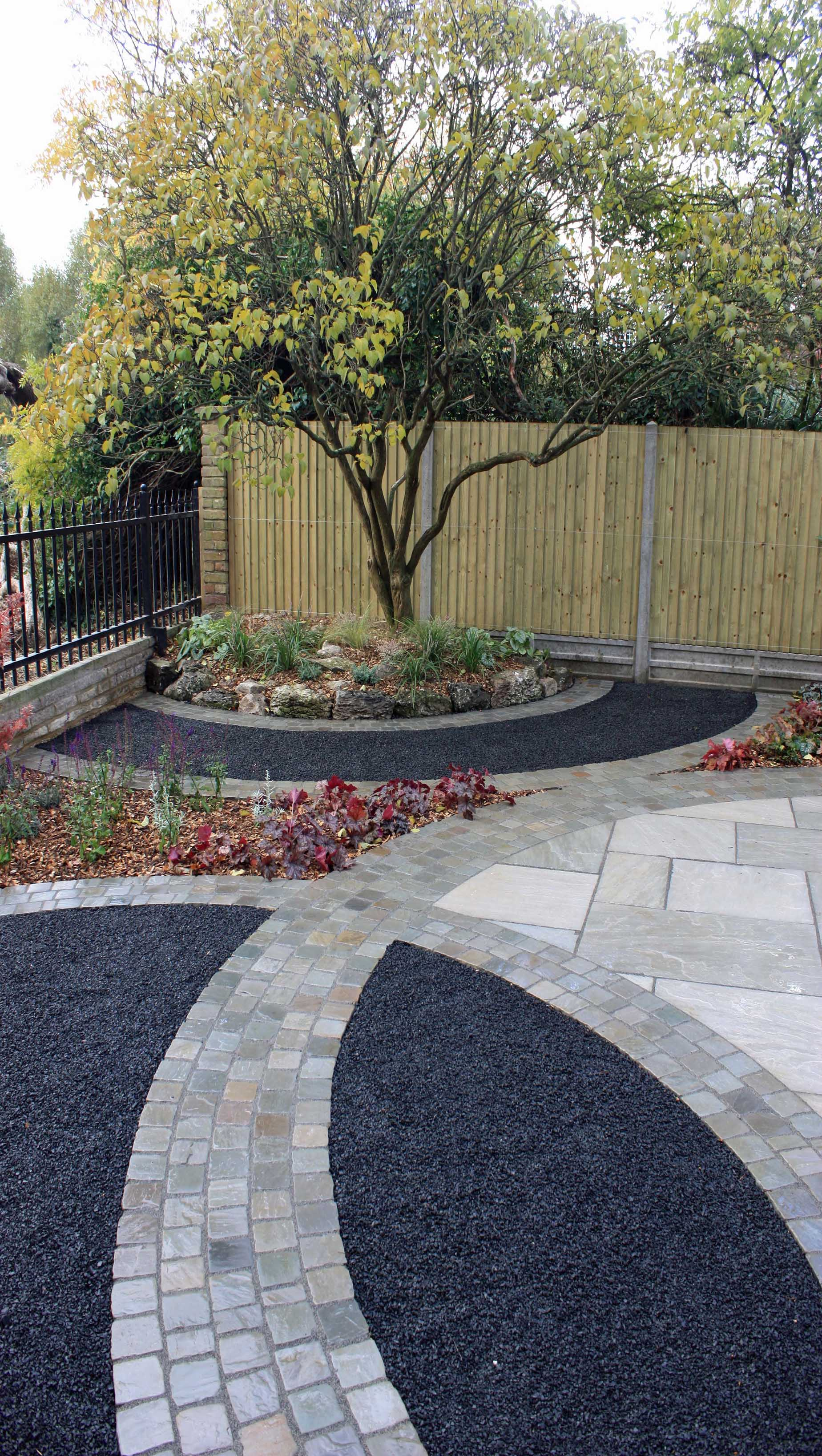 basalt paving with featherboard fencing