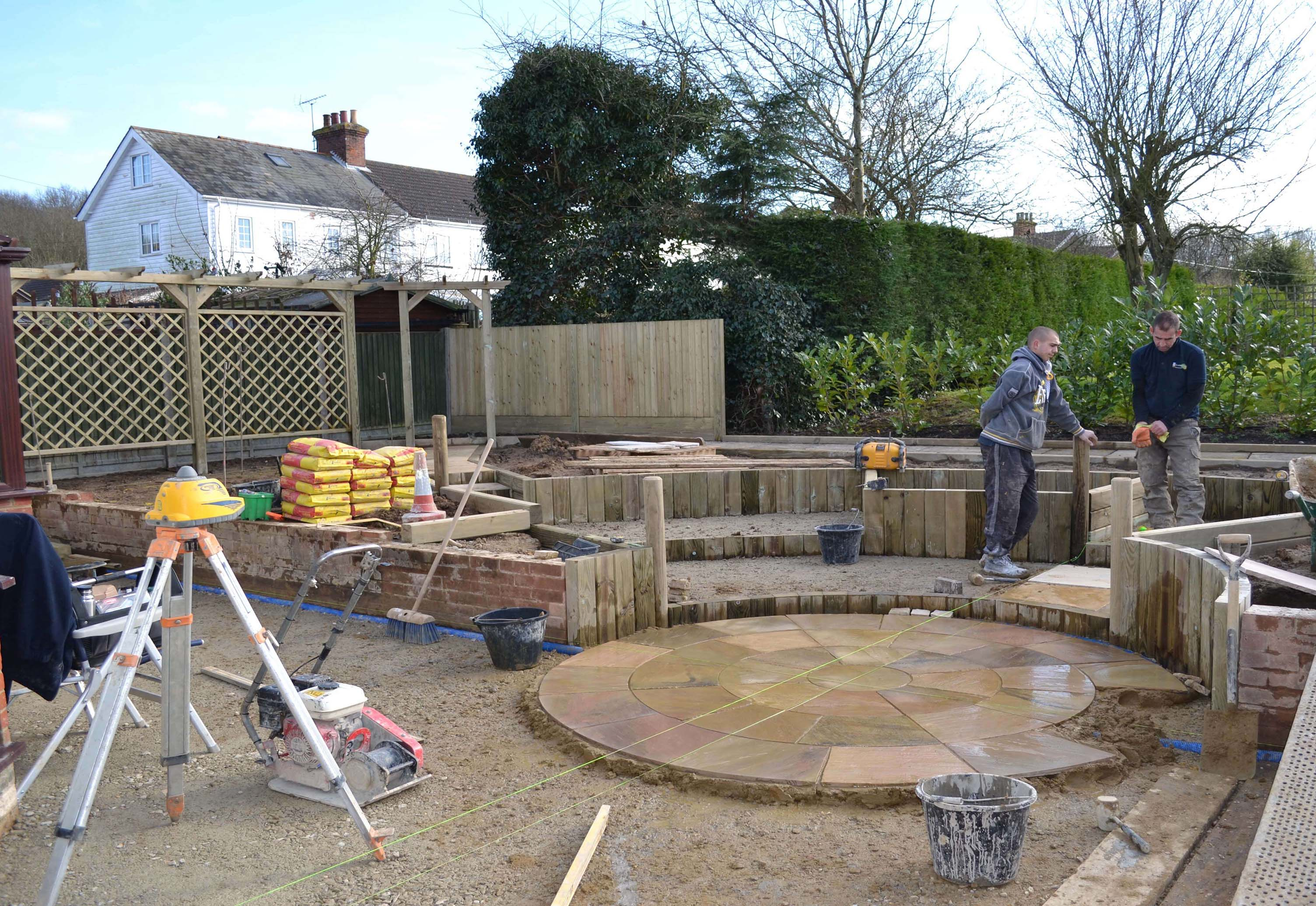 Building the central paving feature with trellis and fencing in the background