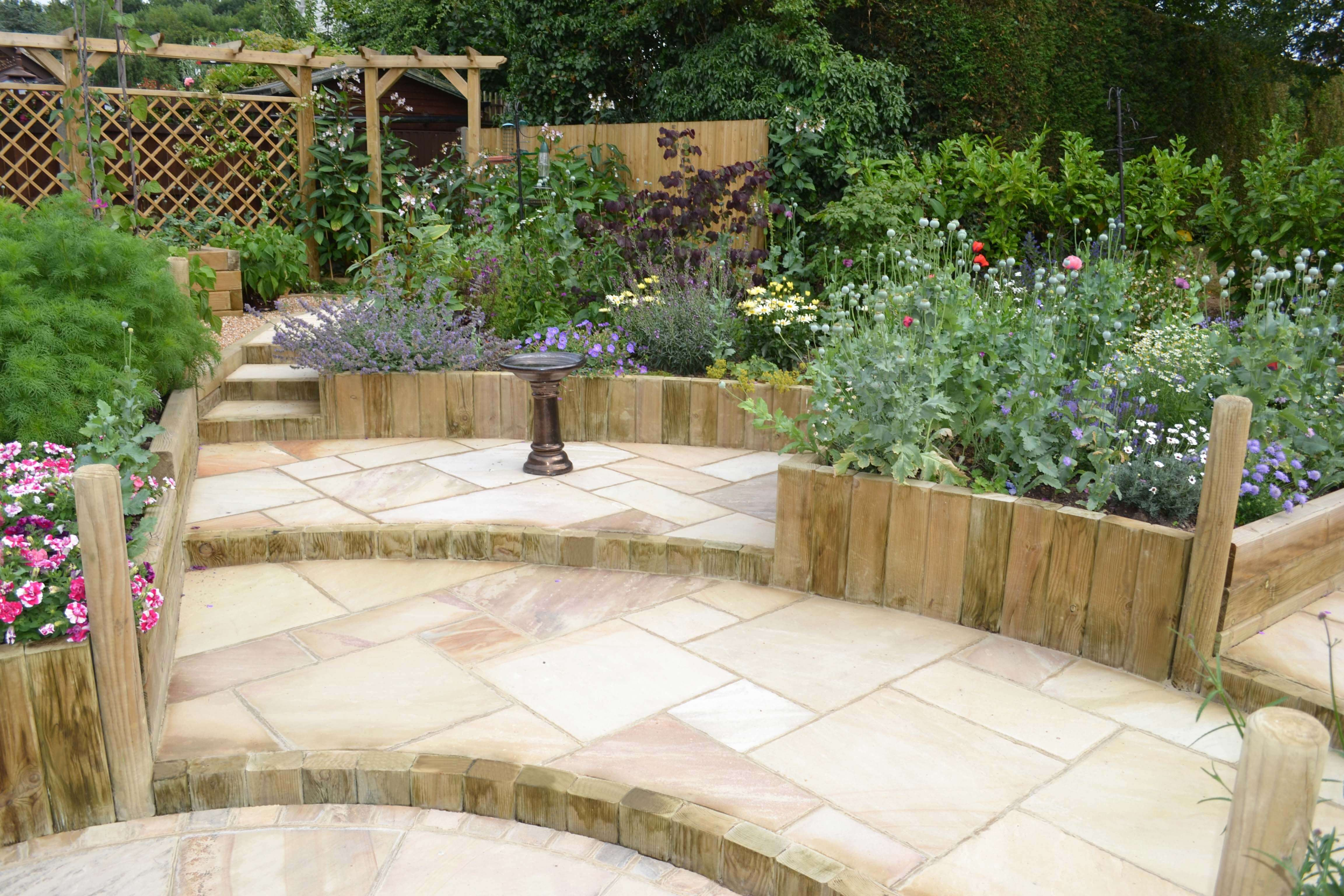 garden with steps from landscape timbers and single wooden pergola