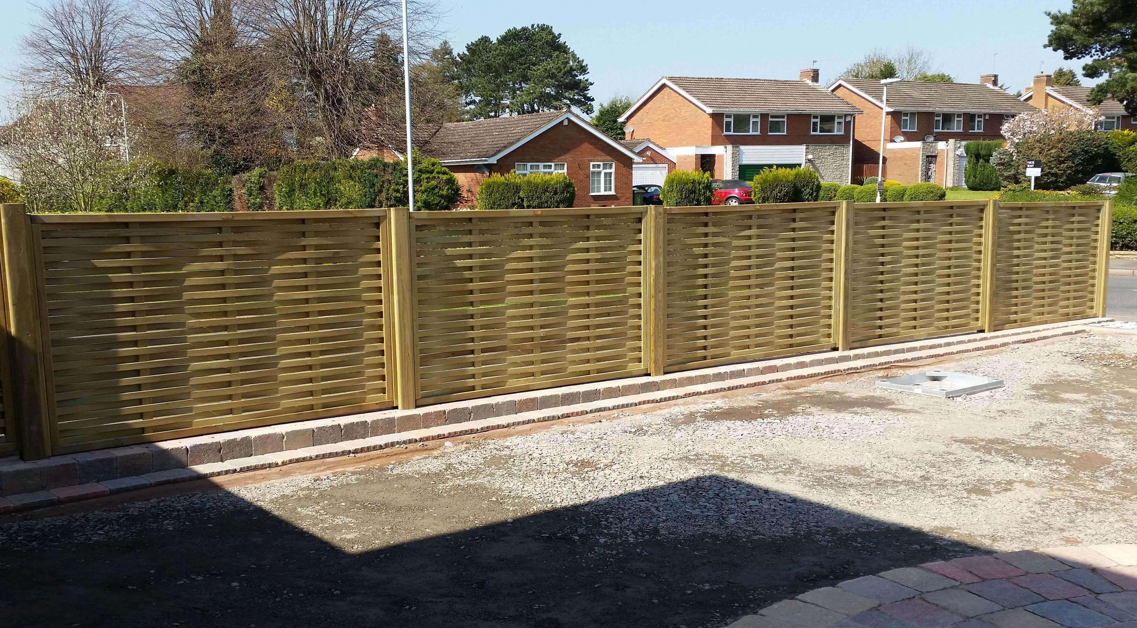 Woven fence panels installed on drive